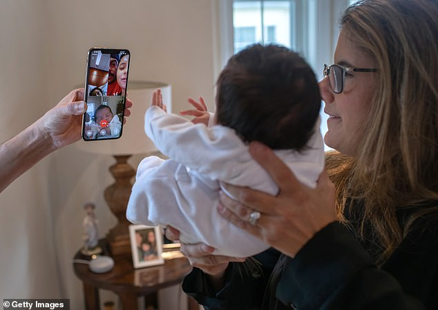An excess 267,000 infant deaths were reported in 2020, 7% higher than the 248,000 fatalities initially projected last year. Pictured:Stamford Elementary school teacher Luciana Lira, 42, holds baby Neysel, then two weeks, to show his mother Zully, a Guatemalan asylum seeker, and her son Junior, 7, via Zoom in Connecticut, April 2020