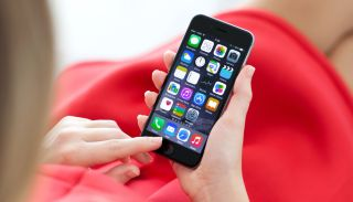 Close-up of an iPhone 6 in the hands of a woman wearing a red dress.